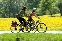Germany, Bavaria, Man and woman riding bicycle