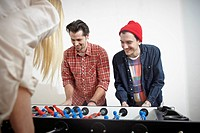 Germany, Cologne, Men and woman playing table soccer, smiling (thumbnail)