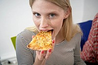 Germany, Cologne, Young woman eating pizza