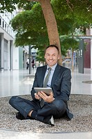 Germany, Leipzig, Businessman sitting at tree with digital tablet