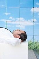 Germany, Leipzig, Businessman resting on cubes