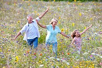 Smiling senior couple with arms outstretched following granddaughter through field of wildflowers