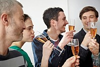 Germany, Cologne, Men and women toasting with champagne in office