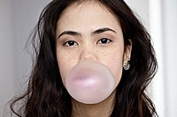 Germany, Cologne, Young woman blowing bubble gum