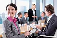 Businesswoman reviewing report on digital tablet in conference room