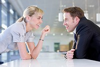Happy businessman and businesswoman talking face to face in office