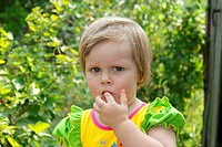 Cute little girl with blond hair in the garden