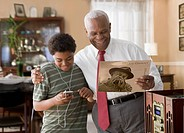 Black grandson and grandfather listening to record player