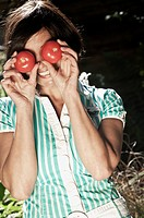 Austria, Salzburg, Flachau, Woman holding tomatoes in front of her eyes, smiling