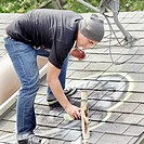 Man tagging roof with graffiti