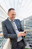 Germany, Leipzig, Businessman using cell phone, smiling