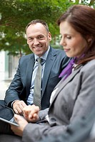 Germany, Leipzig, Business people using digital tablet, smiling