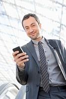 Germany, Leipzig, Businessman using cell phone on escalator, portrait