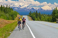 Cyclists on the Glenn Highway with Mt. Drum of the Wrangell Mountains in background, near Glenallen, Southcentral Alaska, Summer