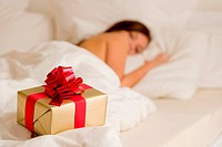 Surprise present _ young woman sleeping in white bedroom