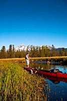 Man with a kayak fishing from the shore of Rabbit Slough in the Palmer Haystack Flats wildlife refuge, Matanuska_Susitna Valley, Southcentral Alaska, ...