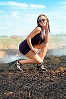 Sexy young brunette in the burning field