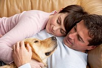Portrait Of Couple Relaxing On Sofa With Pet Dog At Home