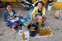 Two women filling mead, honey wine into bottles, Vientiane, Laos, Indochina, Asia