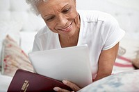 Older woman reading Bible and tablet computer