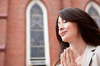 Close up of smiling woman praying
