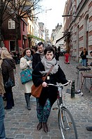 Woman walk with her bike in the street of Brussels, Belgium