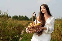 beautiful woman at the meadow with basket with apples