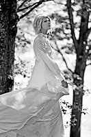 Young woman with short blonde hair wearing a white gown walking through the woods alone