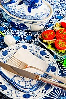 Blue crockery with silver cutlery and tomatoes with parsley