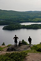 Camden, Maine, United States of America..Three hikers rest at the top of a mountain in Maine.