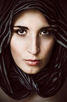Close_up portrait of a young woman with pale skin and brown eyes, with a scarf around her face staring at the camera