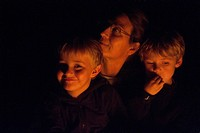 Valparaiso, Nebraska..A campfire lights up the faces of a mother and her two young children.