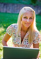 Beautiful young blonde using laptop in sunlit nature, smiling at the camera.