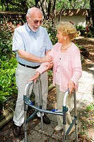 Senior couple outdoors. She´s in a walker and he´s helping her.