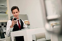 Businessman text messaging on the phone during tea break