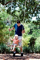 father and smiling happy son on a swing