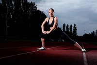 Fitness warm up stretch for beautiful young athlete woman on athletics running track wearing black lycra sports outfit and running spikes. Dark grey c...