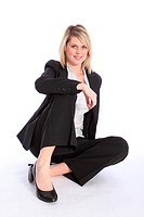 Beautiful young blonde business woman wearing a smart black suit, sitting relaxed and confident on the floor.