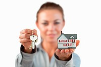 Miniature house and keys being presented by female estate agent against a white background