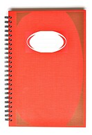 Red rectangular notebook with name lable on cover.