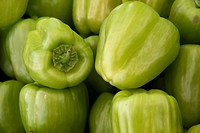 Green bell peppers on a counter in an open marketplace