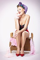 Young woman wearing hair curlers and hot pants sitting on a laundry basket while talking on a telephone, pin-up