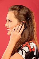 A beautiful dark_haired woman in profile, said by mobile phone on a red background