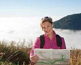 Smiling woman holding a map of trails, Black Forest, Baden-Wuerttemberg, Germany, Europe