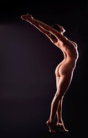 naked yong woman in dark stand on hands _ yoga asana