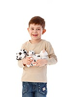 Sweet little boy holding dog in hands, smiling happily.
