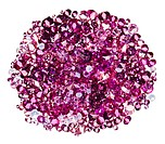 Many small ruby diamond jewel stones heap isolated on white