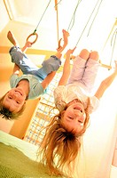 two kids playing hanging on gymnastic rings