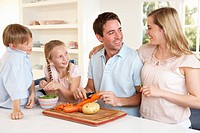 Happy family peeling vegetables in kitchen