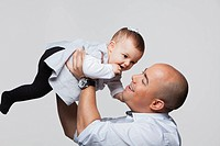 Father holding baby girl up..